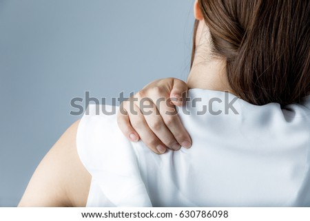 young woman having horribly stiff shoulders