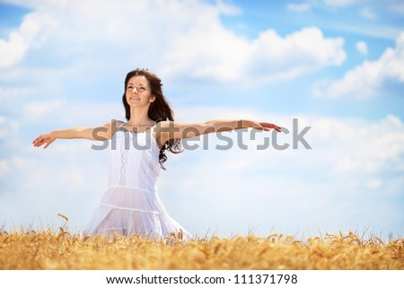 Young woman having joy in  golden wheat field