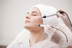 Young woman having micro current galvanic facial treatment with electrodes for lifting face. Concept preventing acne and oily skin problems.