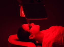 Young woman having red LED light facial therapy treatment in beauty salon. Beauty and wellness concept