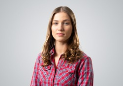 Young woman having serious and calm face. Caucasian female student has confident facial expression. Portrait of girl wears red checkered shirt on grey background. People emotion and expression.