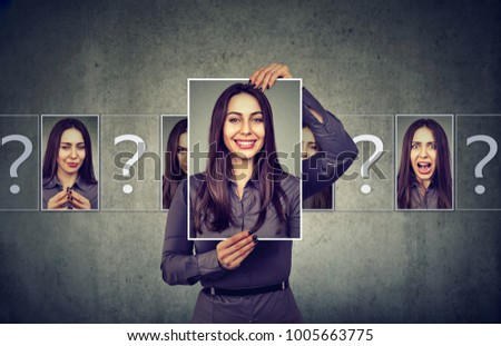 Young woman having split personality while posing with photos of different emotions.  #1005663775