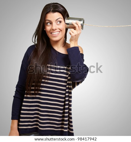 Young woman hearing using a metal tin can over a grey background