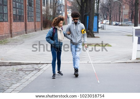 Young Woman Helping Blind Man With White Stick While Crossing Road #1023018754