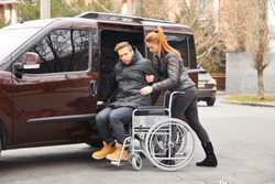 Young woman helping handicapped man to sit in wheelchair
