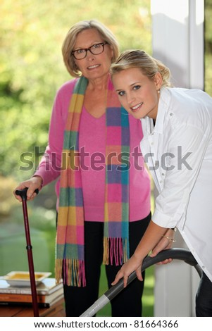 young woman helping senior to clean the house