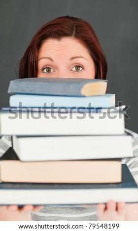Young woman hiding behind a stack of books in a classroom
