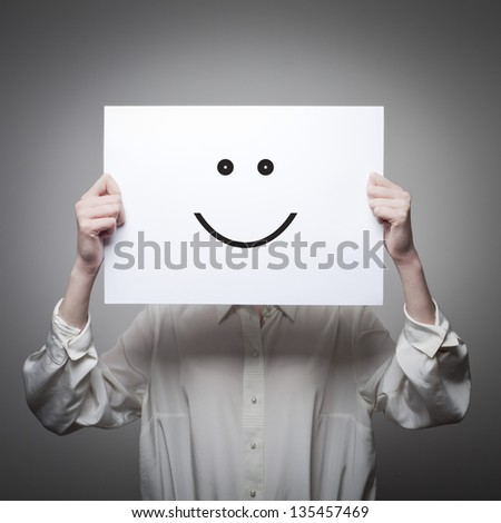 Young woman hiding her face with a white paper with a smiley face on it