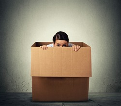 Young woman hiding in a carton box