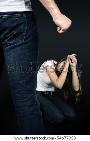 Young woman hiding in from her partner - domestic violence concept - stock photo