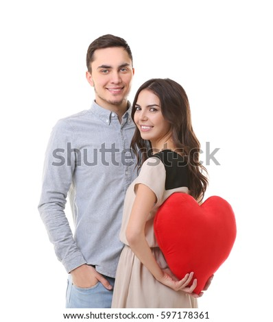 Young woman hiding pillow in shape heart for boyfriend behind back on white background #597178361