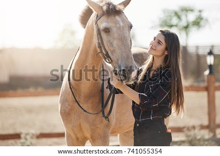 Young woman highly skilled equine foot care professional walking out a horse on animal farm on a sunny summer day. - Shutterstock ID 741055354