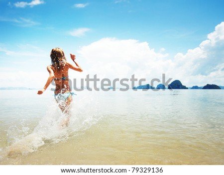 Young woman hight speed running into sea with splashes #79329136