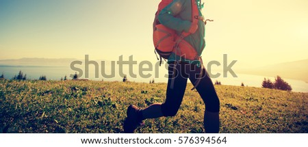 young woman hiker hiking in...