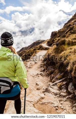 Young woman hiker hiking in Himalaya Mountains in Nepal. Nordic walking, sport and fitness in autumn nature outdoors, beautiful landscape