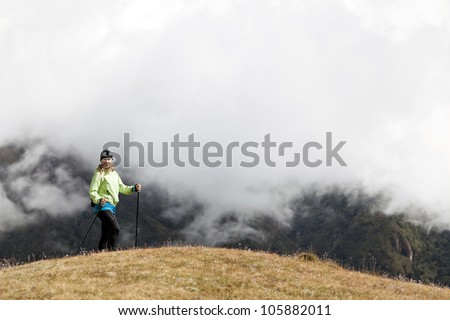 Young woman hiker hiking in Himalaya Mountains in Nepal. Trekking and nordic walking, exercising outdoors.