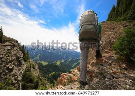 young woman hiker hiking on...