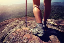 young woman hiker legs on mountain peak cliff