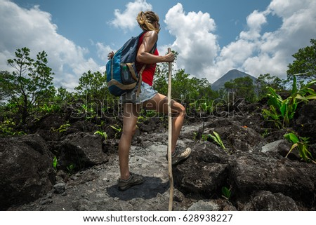 Young woman hiker relaxing on the trail and watching volcano on the horizon #628938227