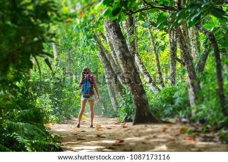 Young woman hiker stands in the tropical lush forest and looks at the trees. Tilt shift effect applied on the edges #1087173116