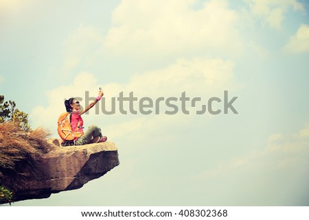 young woman hiker taking photo with cell phone at mountain peak cliff #408302368