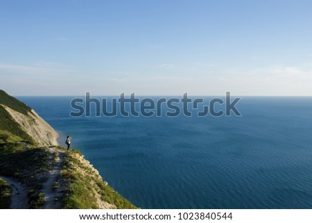 Young woman hiker with backpack standing on cliff and looking forward on the background of the sea, sky. tourist on top of mountain enjoying view. Traveling, freedom and active lifestyle concept