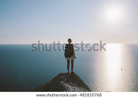 Young woman hiker with backpack standing on cliff and looking forward on the background of the sea, sky. lady tourist on top of a mountain enjoying view.