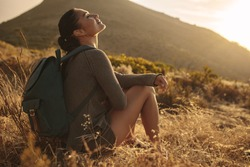 Young woman hiking in countryside sitting and taking rest. Female hiker resting on dry grass field.