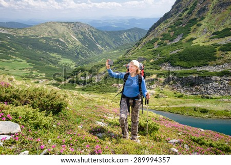 Young woman hiking in the mountains and taking a picture of herself on phone camera
