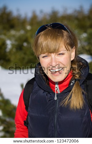 Young woman hiking in winter mountains. Sport and fitness outdoors in forest, beautiful female hiker walking with backpack.