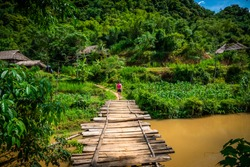 young woman hiking on a wooden bridge in Pu Luong, rural area close to Mai Chau, Vietnam.