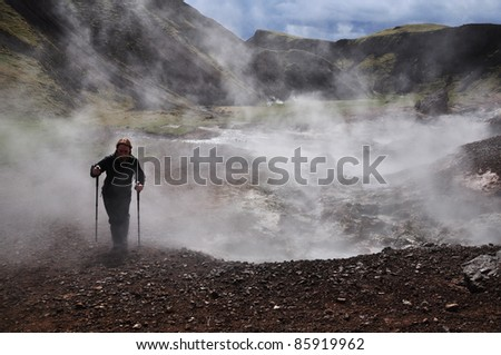 Young woman hiking with trekking sticks in geothermal area, Iceland