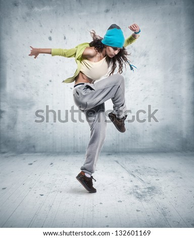 young woman hip hop dancer with grunge wall background texture