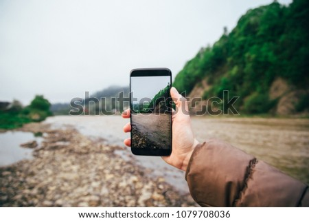 Young woman hipster makes photo of mountain and river landscape on smartphone camera, to share on internet social media through photo application for mobile device.
