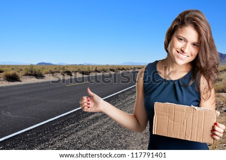 Young woman hitch hiking at a desert road holding a cardboard