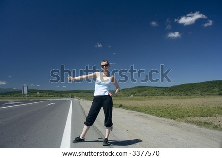 young woman hitchhiking on highway