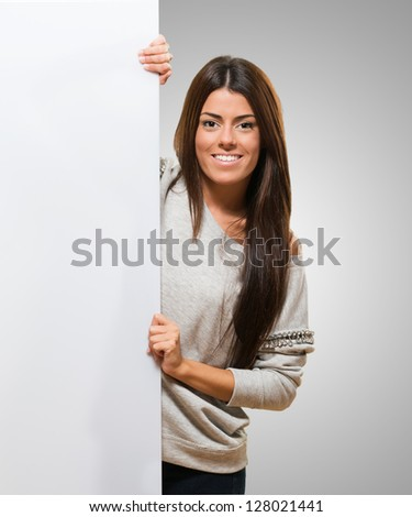 Young Woman Holding A Big Blank Card against a grey background