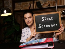 Young woman holding a black chalkboard in hands. Conceptual photo about Stock Screener with written text.