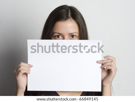 Young woman holding a blank sign in front oh her face