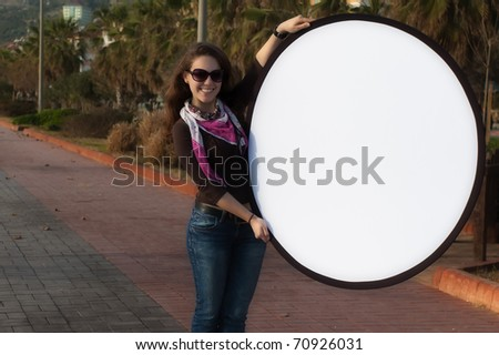 Young woman holding a blank sign on the street