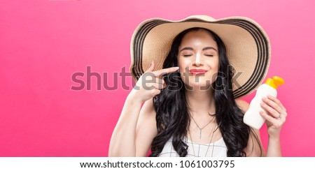 Young woman holding a bottle of sunblock on a solid background #1061003795