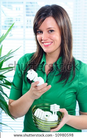 Young Woman Holding A Bowl Of Energy Saving Light Bulbs CFL Compact Fluorescent Light Bulbs For Energy Conservation At Home