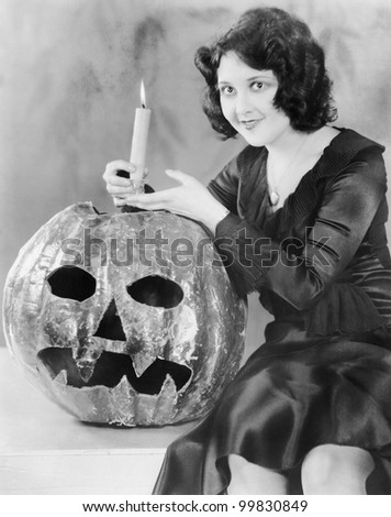 Young woman holding a burning candle on a Jack O' Lantern and smiling