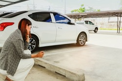Young woman holding a car key sits dumbfounded at her own parking space that is empty as her car is stolen, while she runs errands : Car insurance theft in a shopping mall concept