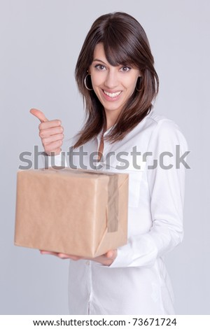 Young woman holding a cardboard box with a happy expression and doing the ok hand sign