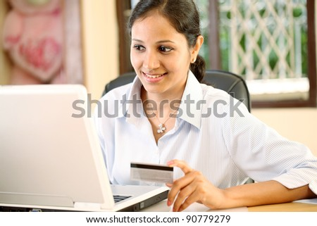 Young woman holding a credit card and doing online shopping