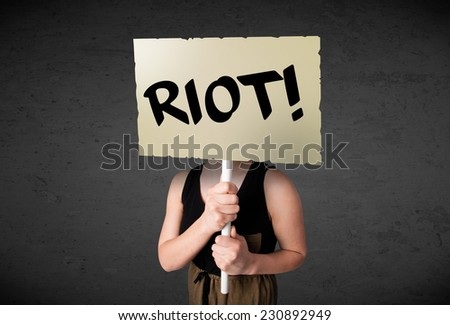 Young woman holding a demonstration board with riot sign in front of her head