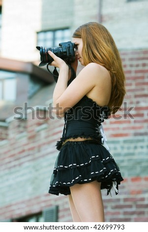 Young woman holding a digital photo camera.