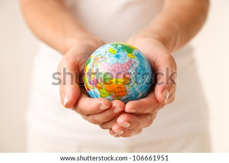 Young woman holding a globe in his hands.
