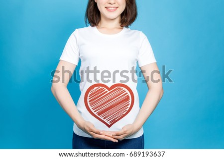 young woman holding a heart symbol. #689193637